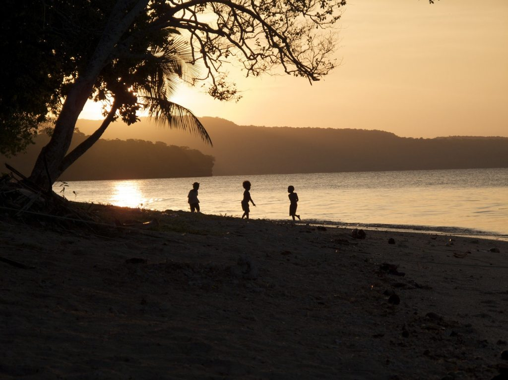 Three Ni-Vanuatu children playing on a beach with a sunset in the background